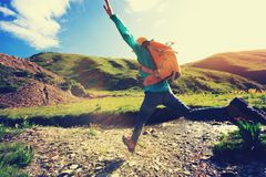 Woman jumping over high altitude river. Backpacking woman jumping over high altitude river royalty free stock images