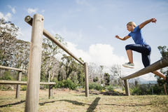 Woman jumping over the hurdles during obstacle course. In boot camp Stock Photo