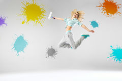Woman jumping and paiting walls Royalty Free Stock Images