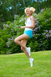 Woman jumping in the park Stock Images