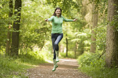 Woman jumping on path smiling Stock Photography