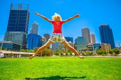 Woman jumping in Perth downtown stock images