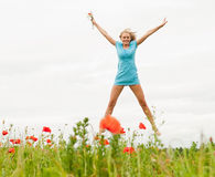 Woman jumping in a poppy field Royalty Free Stock Photography