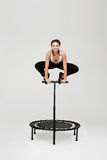 Woman jumping on rebounder with bending knees holding handle Royalty Free Stock Photo