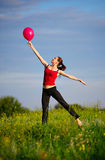 Woman jumping with a red balloon stock images