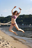Woman jumping on the river beach Stock Photos