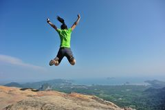 Woman jumping on rocky mountain peak, freedom Stock Photo