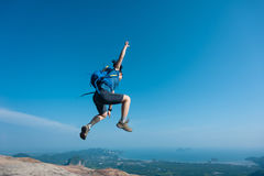 Woman jumping on rocky mountain peak, freedom Royalty Free Stock Images