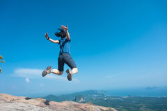 Woman jumping on rocky mountain peak Stock Photos