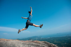 Woman jumping on rocky mountain peak Royalty Free Stock Photo