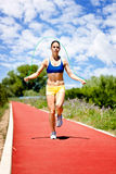 Woman jumping rope. Sporty woman training on jumping rope on track Royalty Free Stock Photo