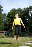 Woman jumping rope in the garden Royalty Free Stock Images