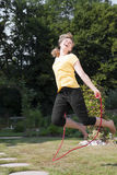 Woman jumping rope in the garden Stock Image