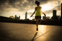 Woman jumping rope at sunrise city building roof. Young fitness woman jumping rope at sunrise city building roof Royalty Free Stock Photography