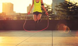 Woman jumping rope at sunrise city building roof. Young woman jumping rope at sunrise city building roof Stock Image