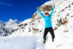 Woman jumping and running in winter mountains Stock Photography