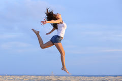 Woman jumping on the sand of the beach. With the horizon in the background Stock Images
