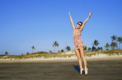 Woman jumping on the sand of beach - Stock Image Stock Photography