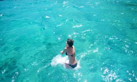 Woman jumping in the sea stock images