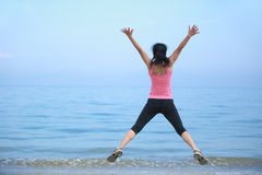 Woman jumping seaside Stock Image