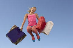 Woman Jumping With Shopping Bags Stock Photography