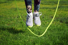 woman jumping on a skipping rope in park Stock Photo