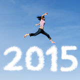 Woman jumping on the sky. Attractive woman jumping on the sky with cloud shaped number 2015 Stock Photos