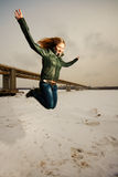 Woman jumping in snow royalty free stock image