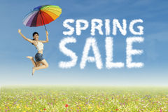 Woman jumping with spring sale clouds Royalty Free Stock Photo