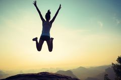 Woman jumping on sunrise rocky mountain peak Royalty Free Stock Image
