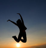 Woman jumping. And sunset silhouette Stock Images