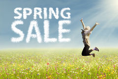 Woman jumping with text of spring sale. Beautiful woman is jumping over colorful flowers during spring sale Stock Photos