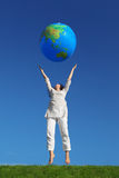 Woman jumping and throwing inflatable globe Stock Image