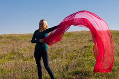 Woman jumping with tissue into the field against Stock Photography