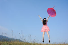 Woman jumping to blue sky  with red umbrella Royalty Free Stock Photos
