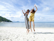 Woman jumping together on sand beach Stock Image