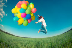 Woman jumping with toy balloons in spring field. Happy girl jumping with colorful toy balloons outdoors. Young woman having fun in green spring field against Stock Photo