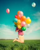 Woman jumping with toy balloons in spring field Stock Image