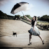 Woman Jumping Up And Catching Cloud With Umbrella Royalty Free Stock Photography