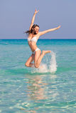 A woman is jumping in water Stock Photos