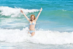 Woman jumping in the waves on tropical beach Royalty Free Stock Images