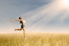 Woman jumping in wheat field Stock Photos