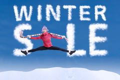 Woman jumping in winter sale. Sign on blue sky Royalty Free Stock Image