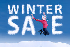Woman jumping with a winter sale sign. Happy woman jumping with a winter sale sign on blue sky Stock Images