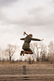 Woman jumping from a wooden bench Stock Image