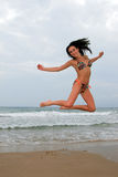 Woman jumpint on the beach Royalty Free Stock Photos