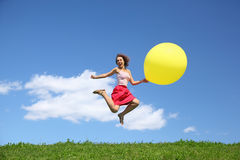 Woman jumps away from grass with large ball Royalty Free Stock Image
