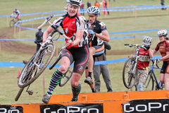 Woman Jumps Barrier at Cycloross Event Stock Photography