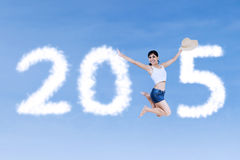 Woman jumps and forming number 2015. Hispanic woman leaps on the sky and forming number 2015 Stock Photo