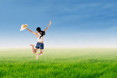 Woman jumps in a green field Stock Photo